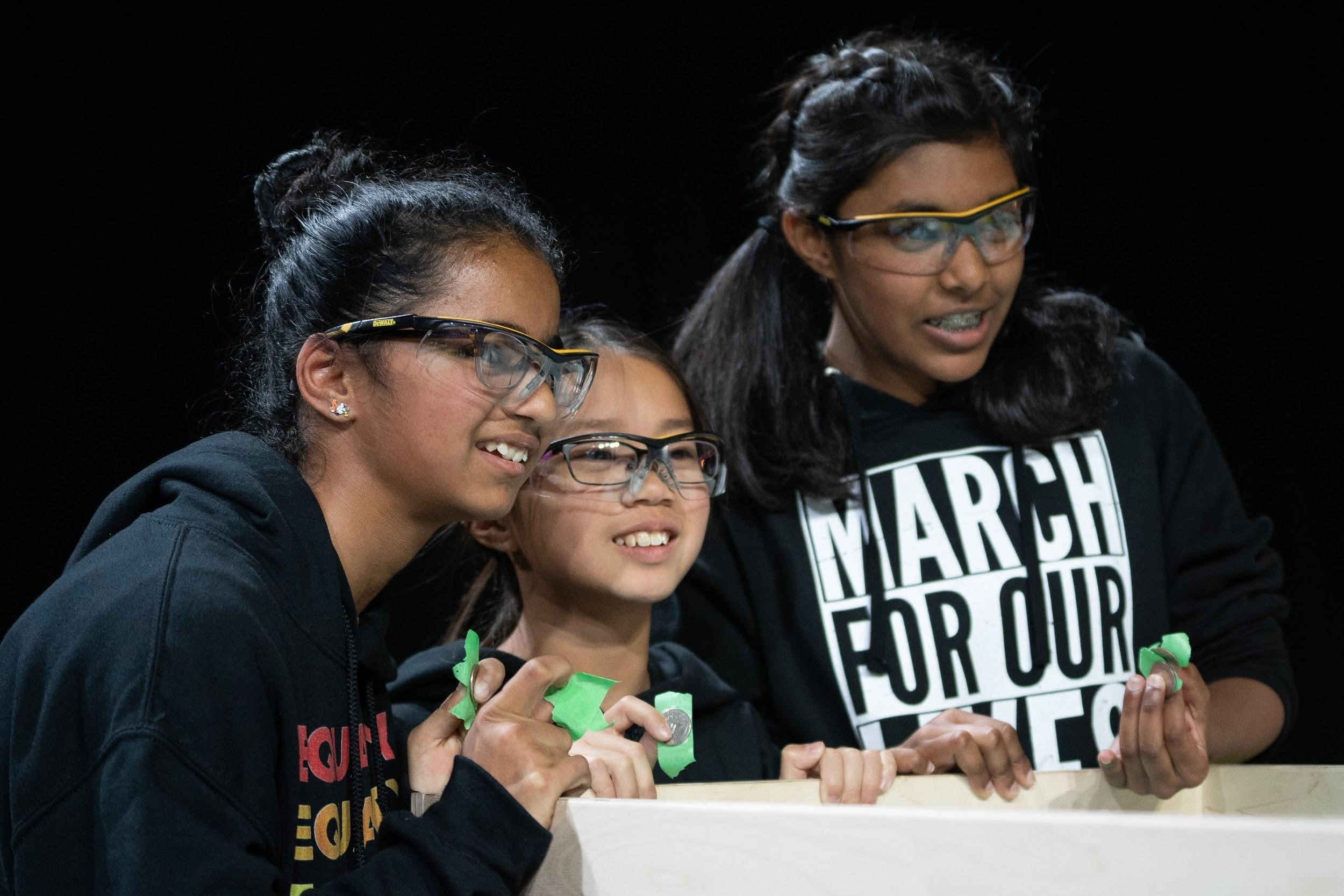 Three young girls wearing safety glasses participate in the tech challenge