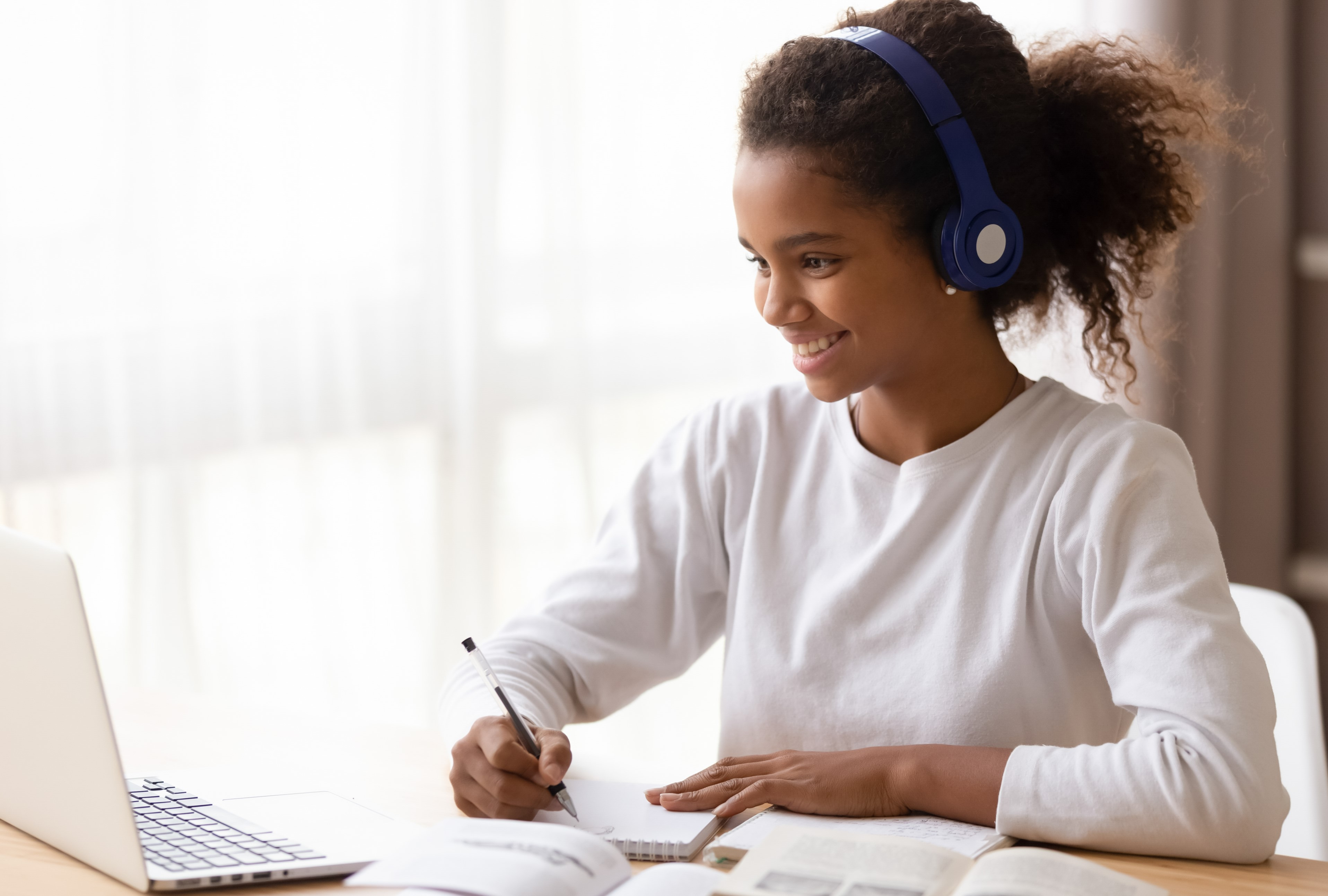 A girl wearing headphones sits in front of a computer