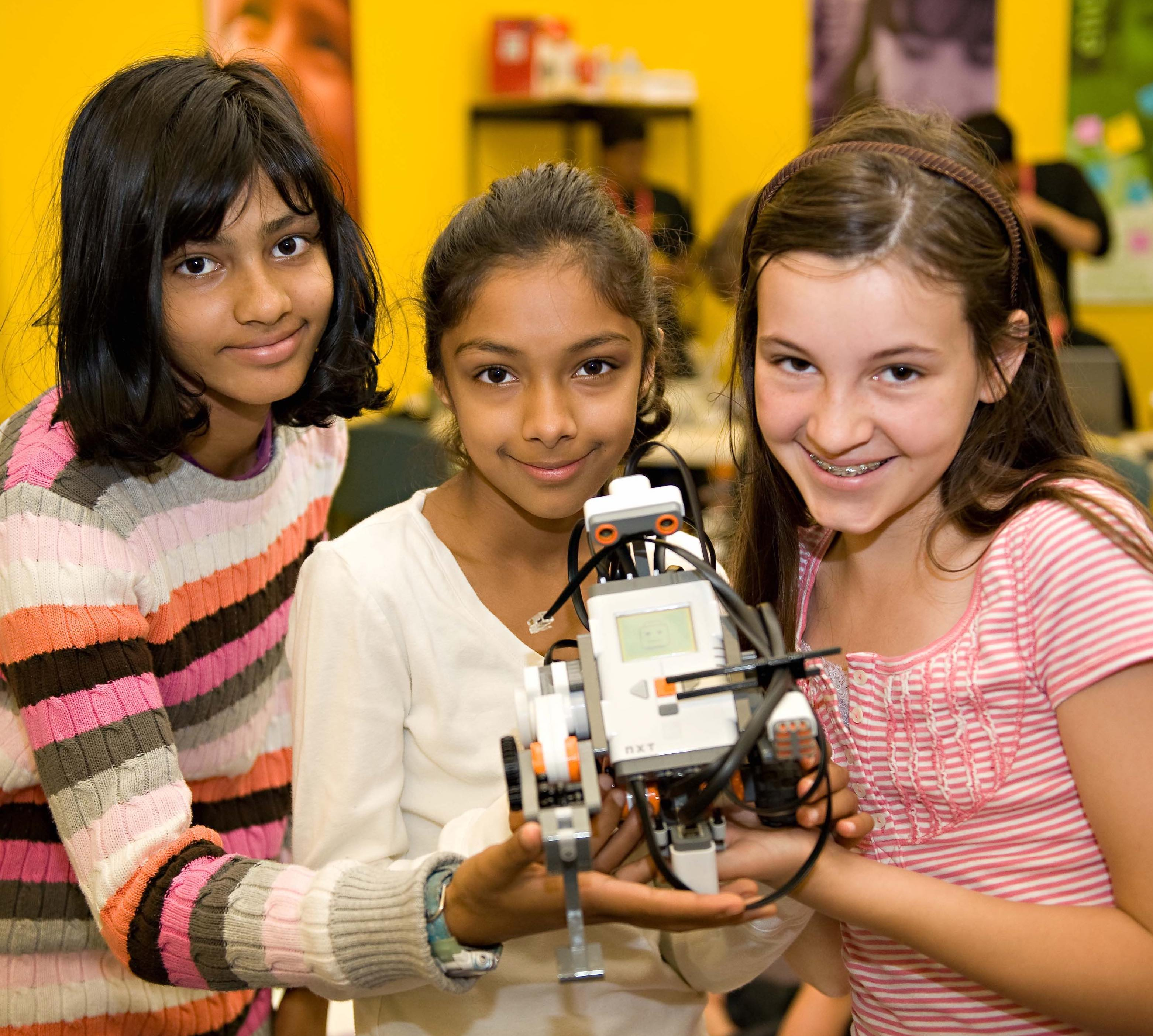A group of young girl students share an engineering project.