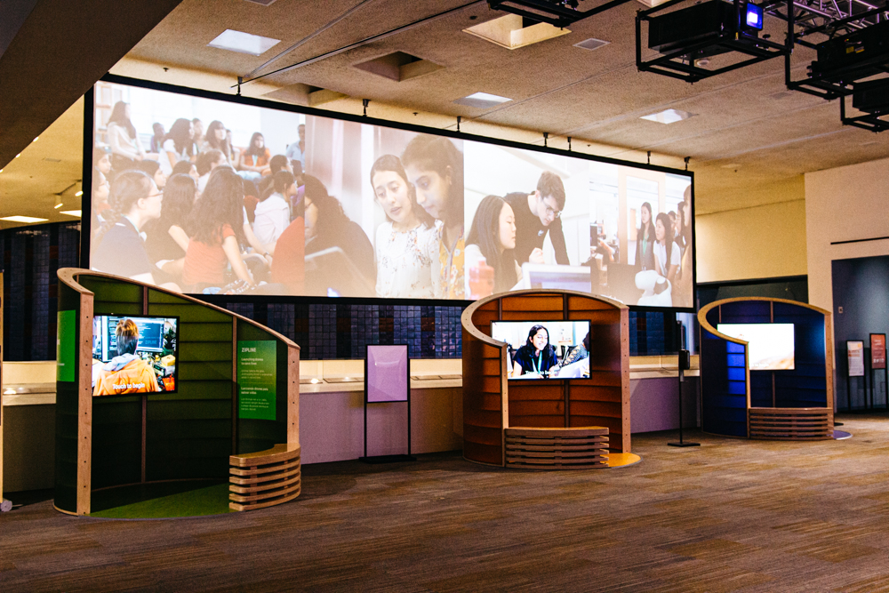 Tech for Global Good exhibit showing kiosks with videos and large projected screen above.